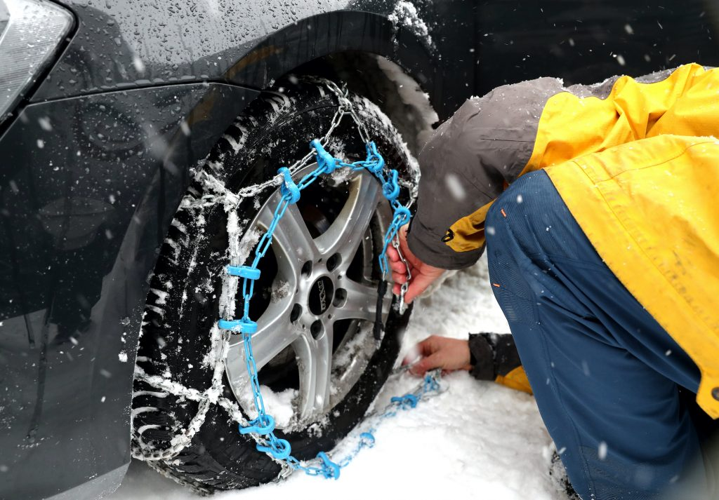 man installing tire chains