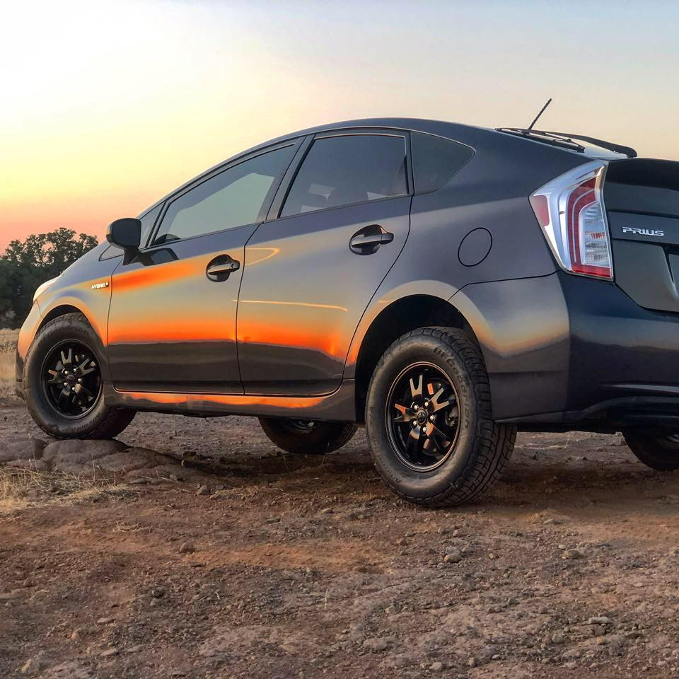 A black Toyota Prius with a lift kit sits on a dirt road.