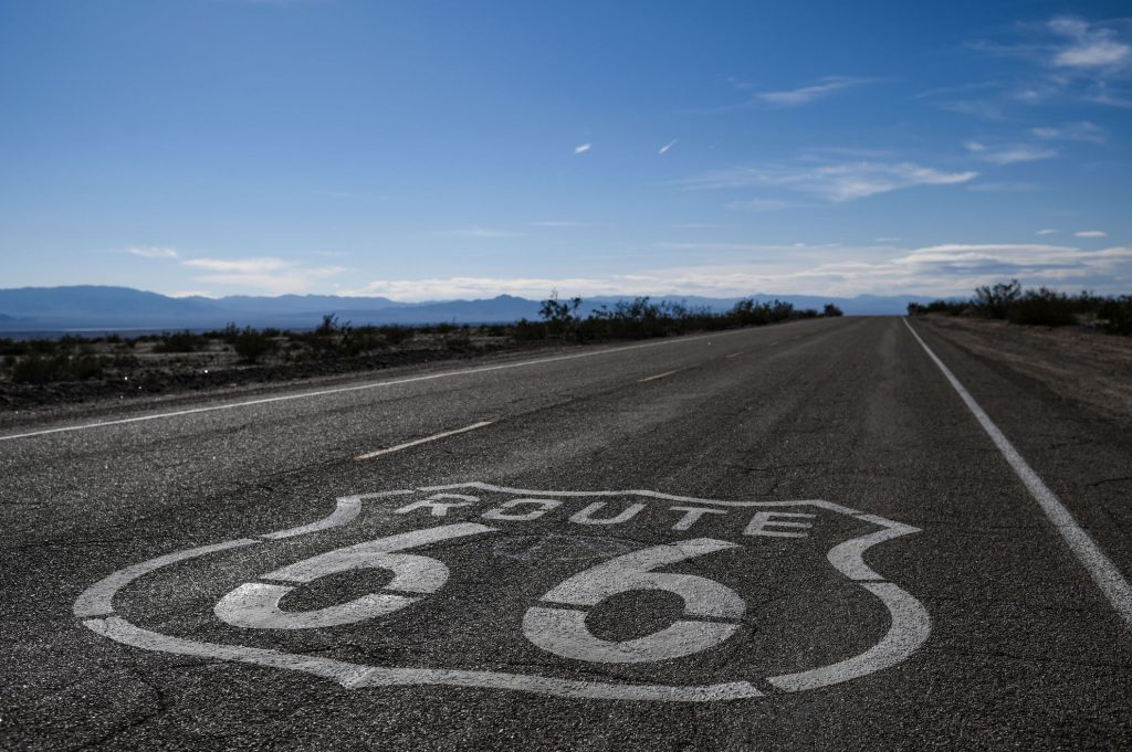 """A """"Route 66"""" sign is painted on the asphalt near Amboy in the Mojave Desert in California. Maybe soon to be unregulated by a speed limit"""