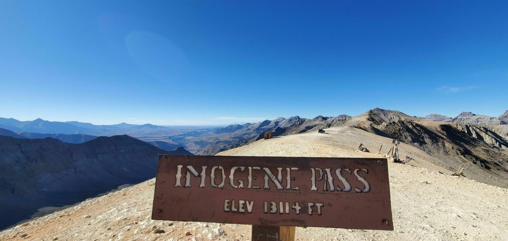 Imogene Pass highest elevation point sign with a mountain view in the background of this pretty off-road trail