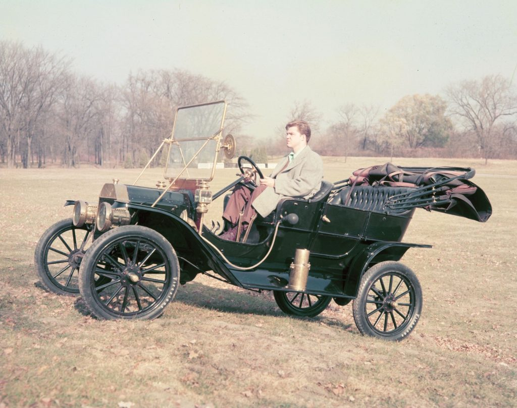 A black 1908 Ford Model T in a field