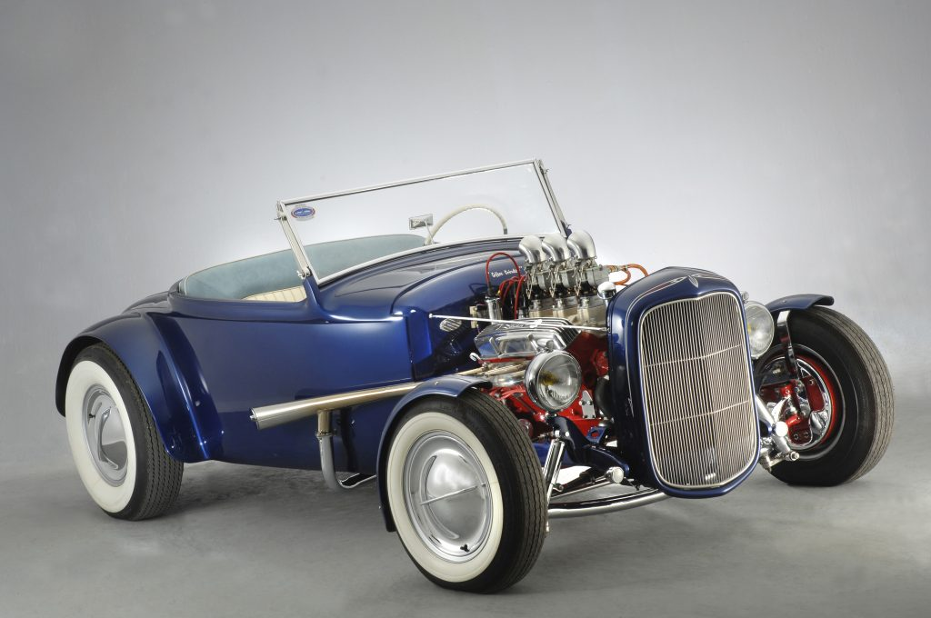 A blue custom hot rod with no hood and white sidewall tires.