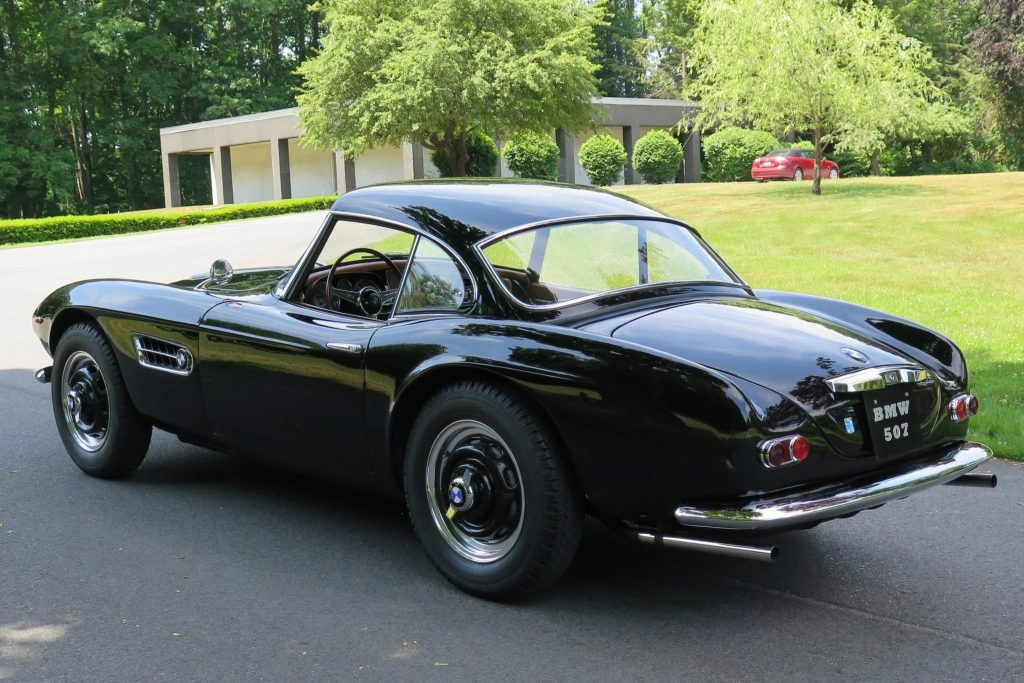 The rear 3/4 view of a black 1957 BMW 507 Series II with its hardtop on