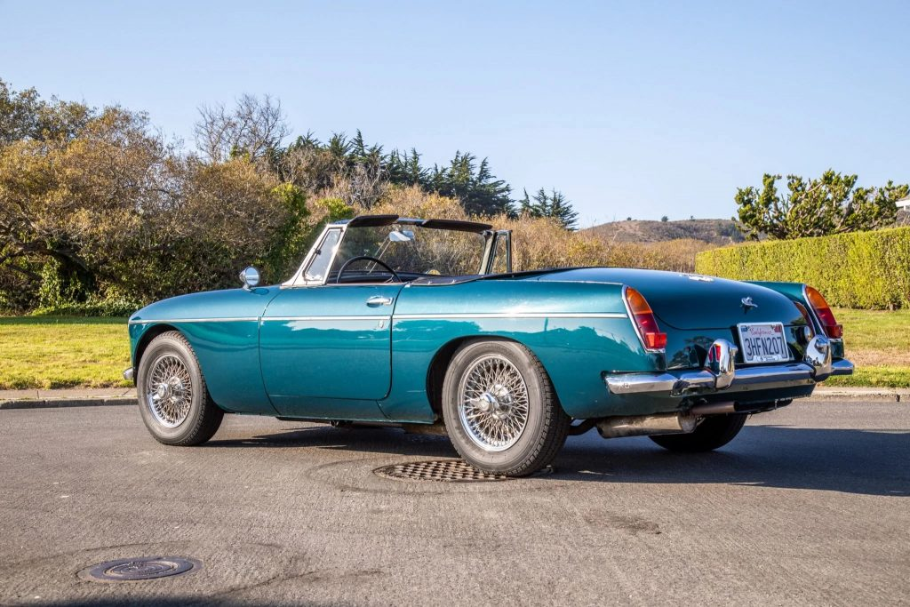 The rear 3/4 view of a turquoise 1965 MG MGB with its top down