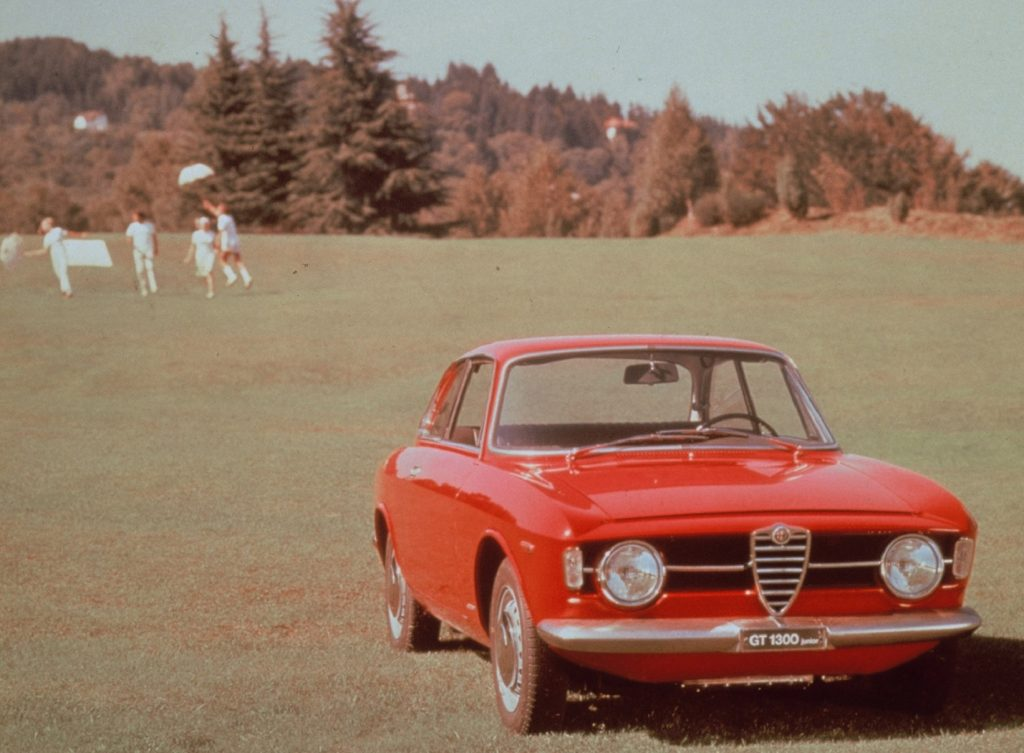 A red 1967 Alfa Romeo GT 1300 Junior in a field