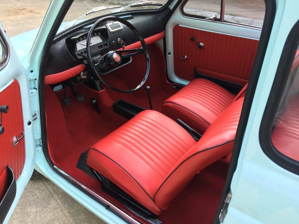 The 1972 Fiat Nuova 500L's red vinyl seats and padded black dashboard