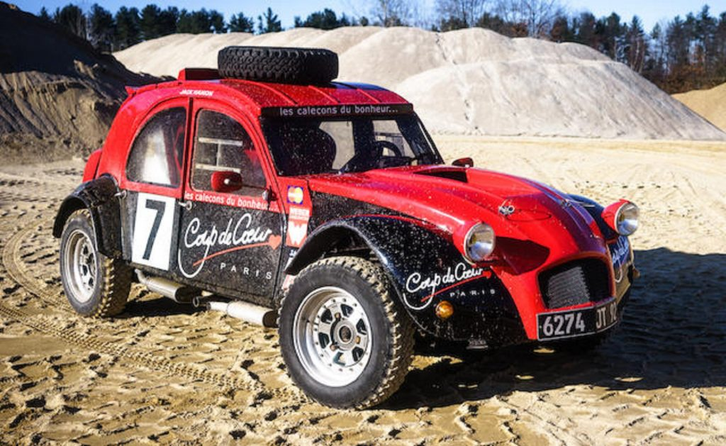 A red-and-black 1974 twin-engine Citroen 2CV 4x4 rally car in a quarry