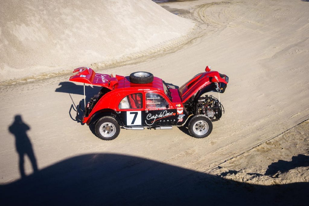 An overhead side view of the black-and-red 1974 twin-engine Citroen 2CV 4x4 rally car in a quarry