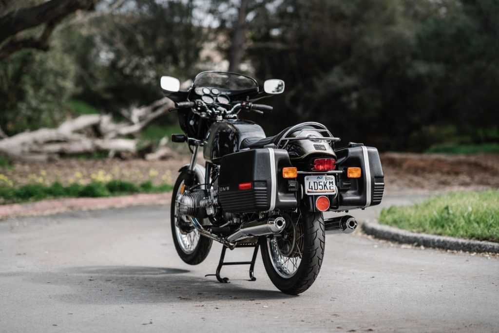 The rear 3/4 view of a black-and-gray 1975 BMW R90S with luggage