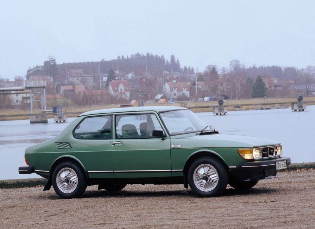 The side view of a green 1978 Saab 99 Turbo by a harbor