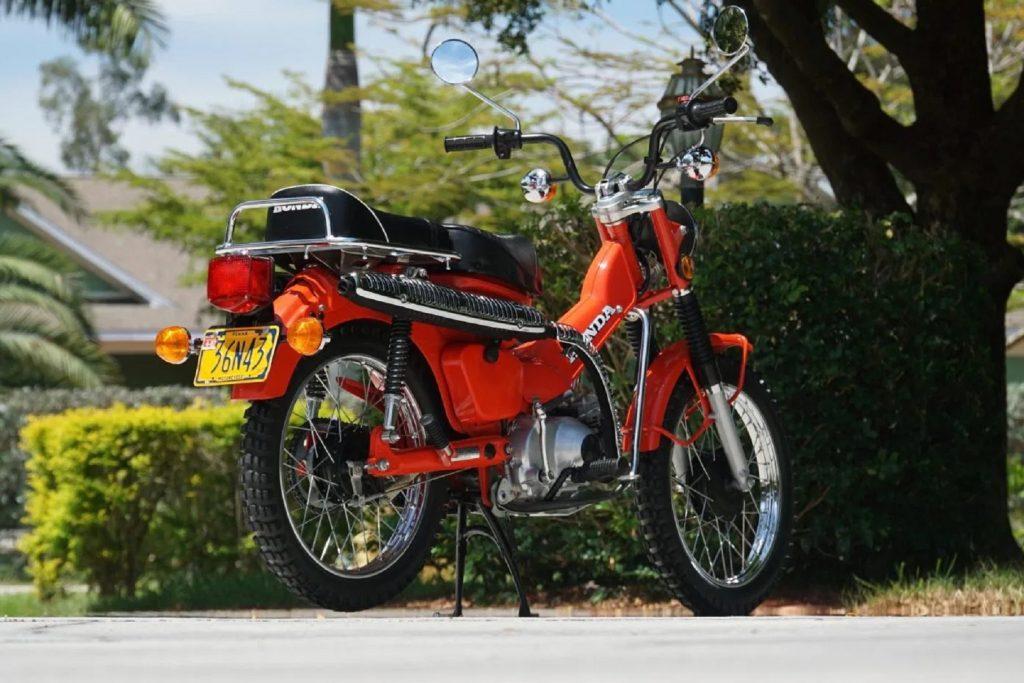 The rear 3/4 view of an orange 1979 Honda CT90 Trail 90
