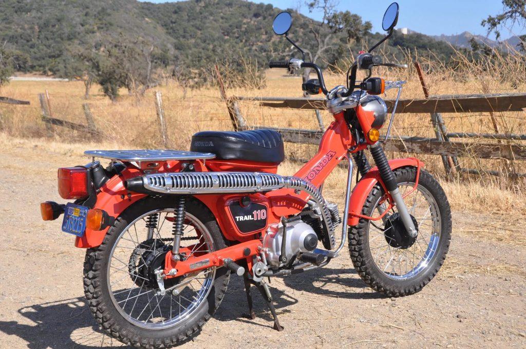 An orange 1981 Honda CT110 Trail 110 on a dirt road