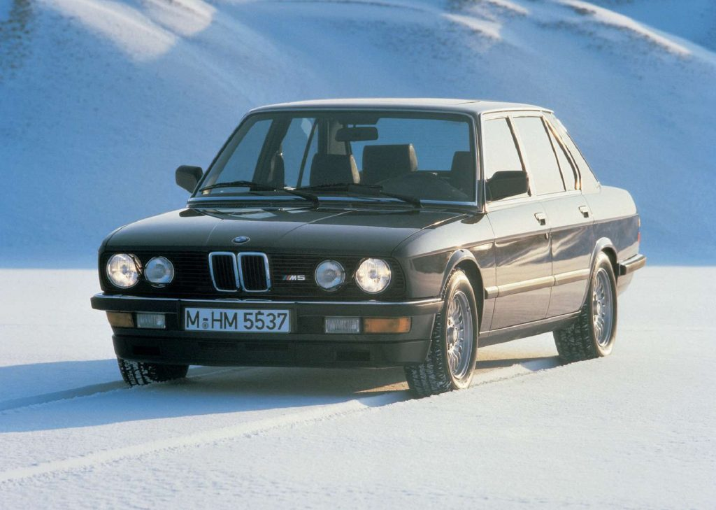 A black 1985 E28 BMW M5 on a snowy mountain