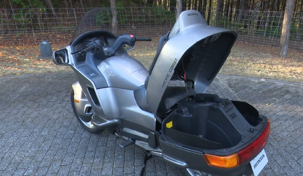 The rear 3/4 view of a gray 1990 Honda PC800 Pacific Coast with its trunk open