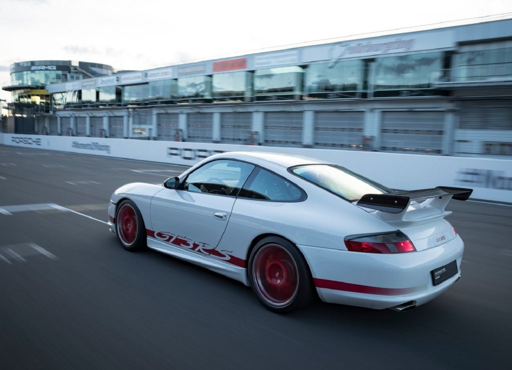 The rear 3/4 view of a white-and-red 2004 Porsche 911 GT3 RS on a track