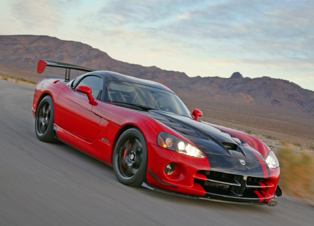 A red 2008 Dodge Viper with a thick black stripe posed in front of a mountain range