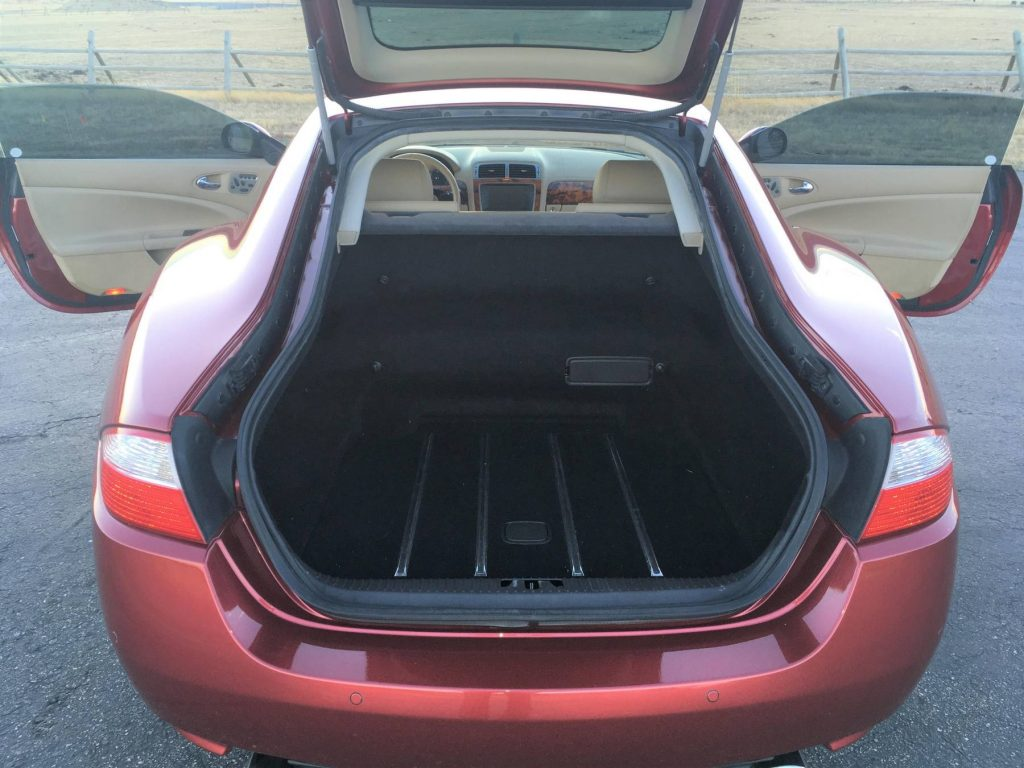 The rear view of a red 2008 Jaguar XK with its tailgate and doors open
