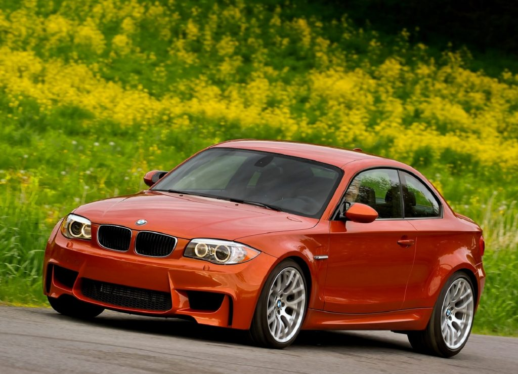 An orange 2011 BMW 1 Series M Coupe by a grassy field