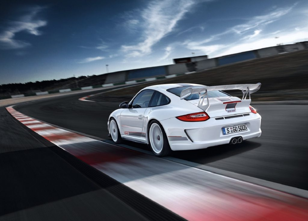 The rear 3/4 view of a white 2012 Porsche 911 GT3 RS 4.0 on a track