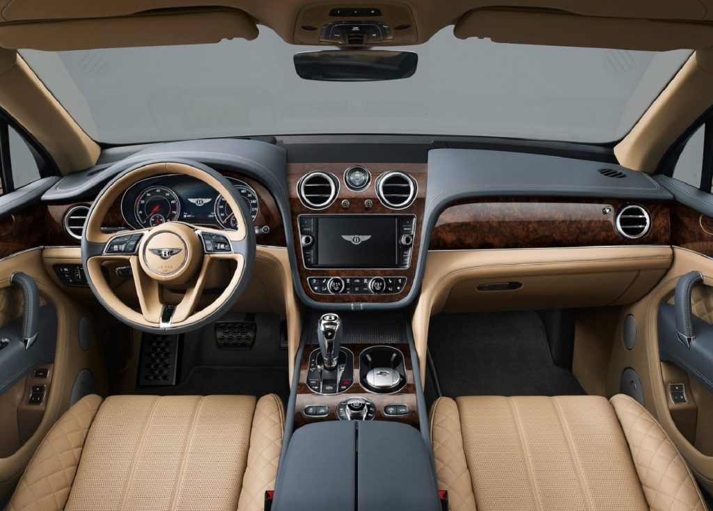The 2017 Bentley Bentayga's wood-trimmed black dash and tan-leather front seats