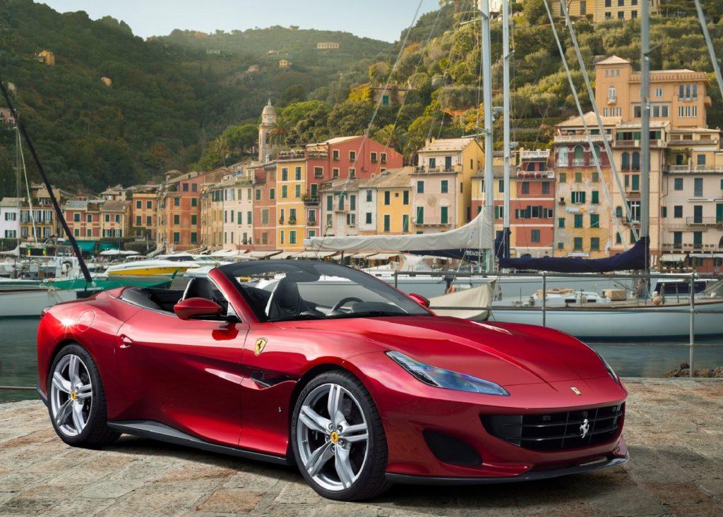 A red 2018 Ferrari Portofino by a harbor