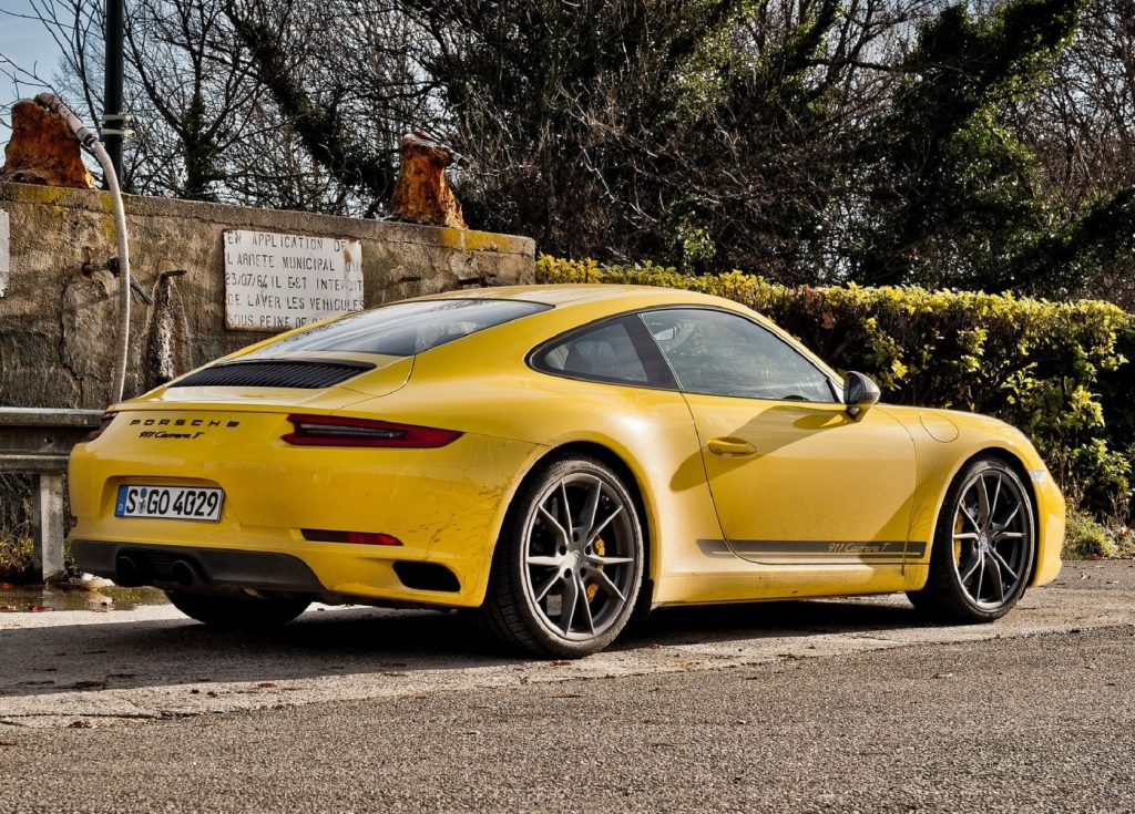 The rear 3/4 view of a yellow 2018 Porsche 911 Carrera T