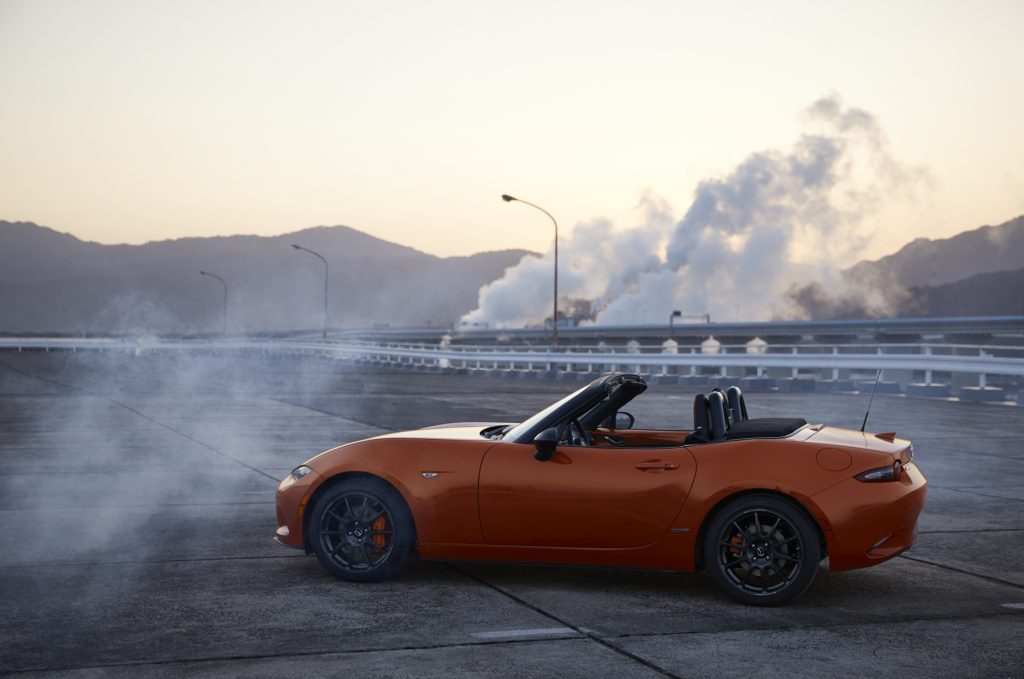 An orange Mazda Miata parked near the side of the road surrounded by smoke