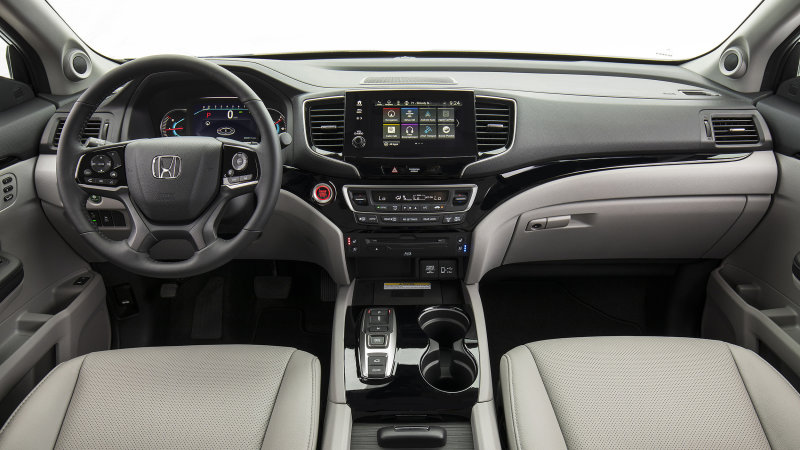 Front seats of the Honda Pilot with beige upholstery.