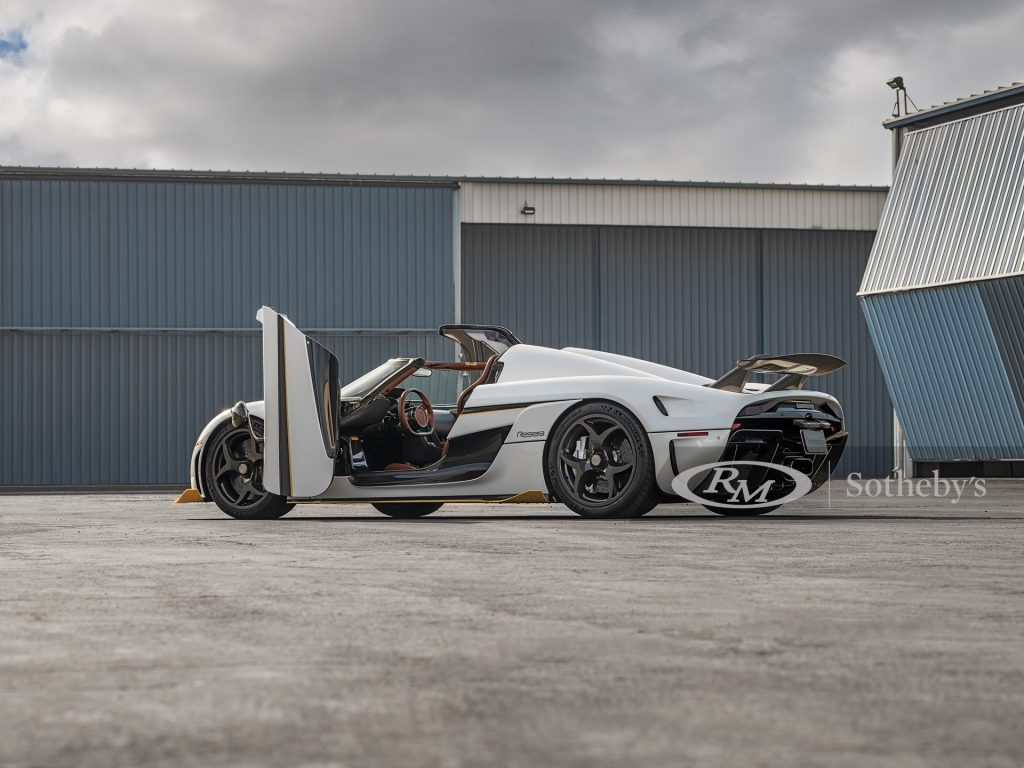 A white 2019 Koenigsigg Regara hypercar sits with its door open, and top off.