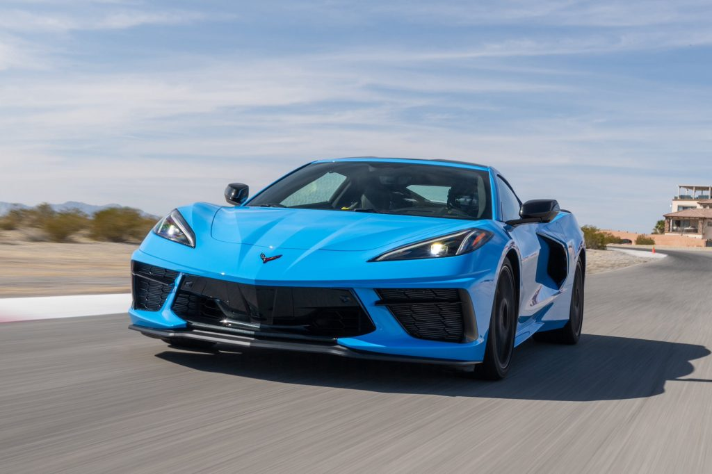 A Rapid Blue 2020 Chevy Corvette travels on a paved surface with an arid landscape, mountains, and a blue sky with wispy clouds in the background