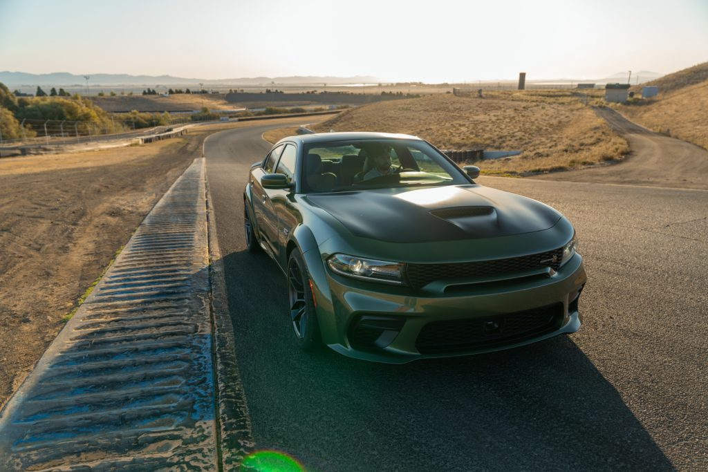 A green and black 2020 Dodge Charger driving down a road