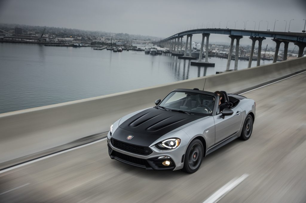 A black and silver 2020 Fiat 124 Spider Abarth driving on a highway