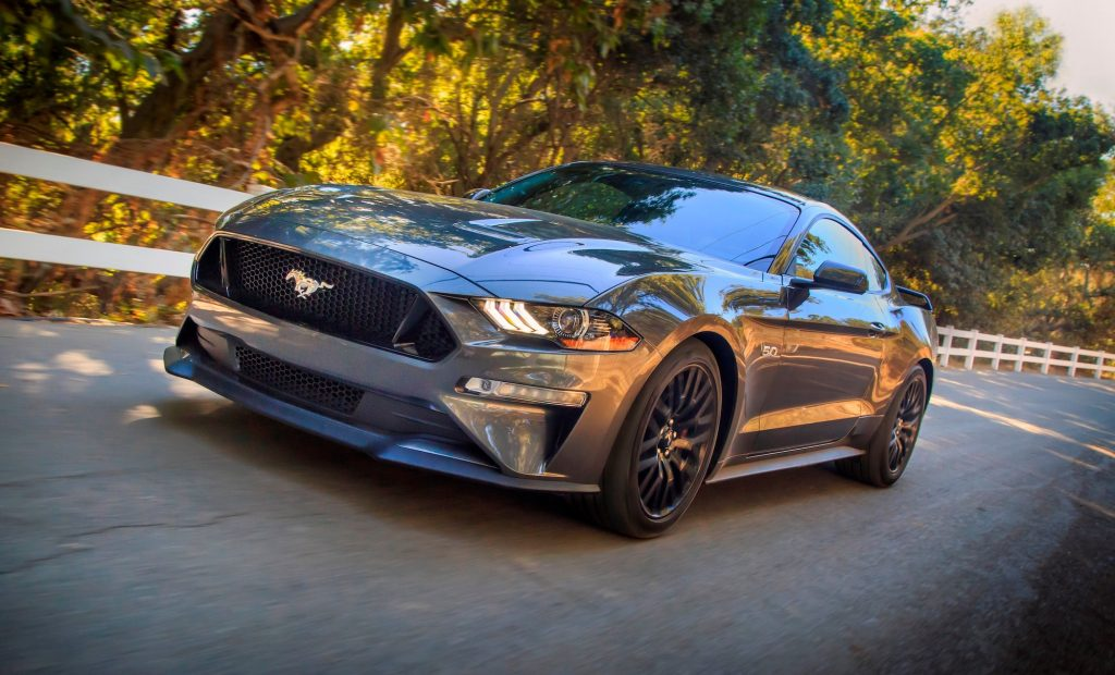 A dark-gray metallic Ford Mustang drives on a tree-lined road