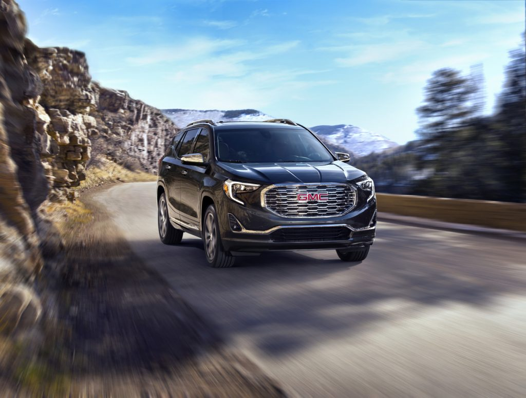 A black 2020 GMC Terrain Denali driving down a road