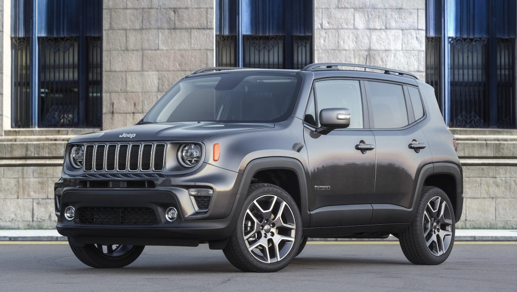 A dark-gray 2020 Jeep Renegade Limited is parked on a street outside a light-gray brick building