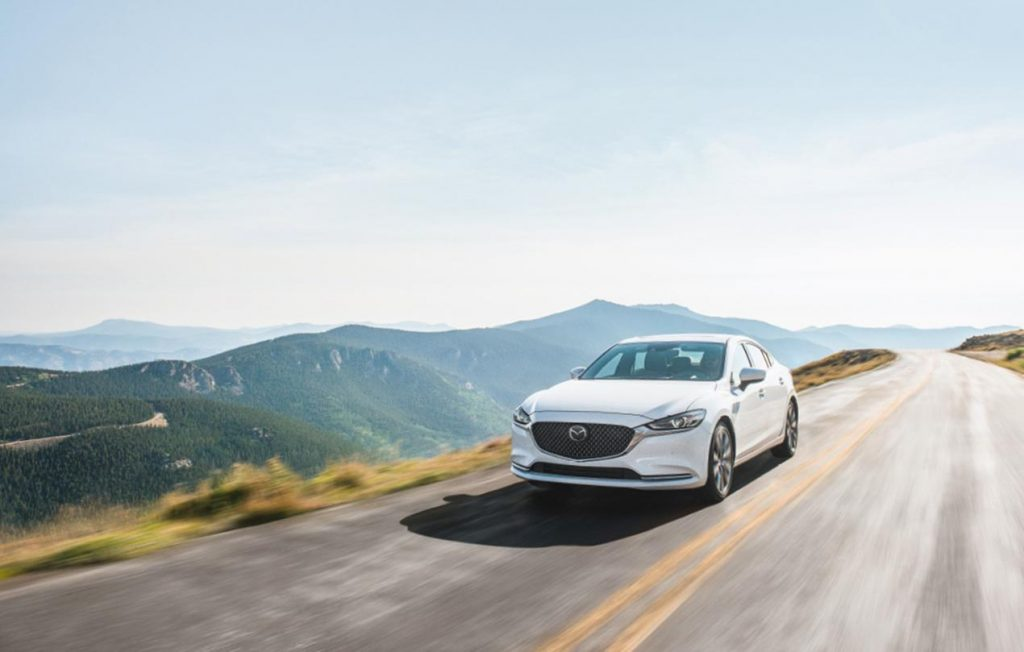 A white 2020 Mazda6 driving down a highway road