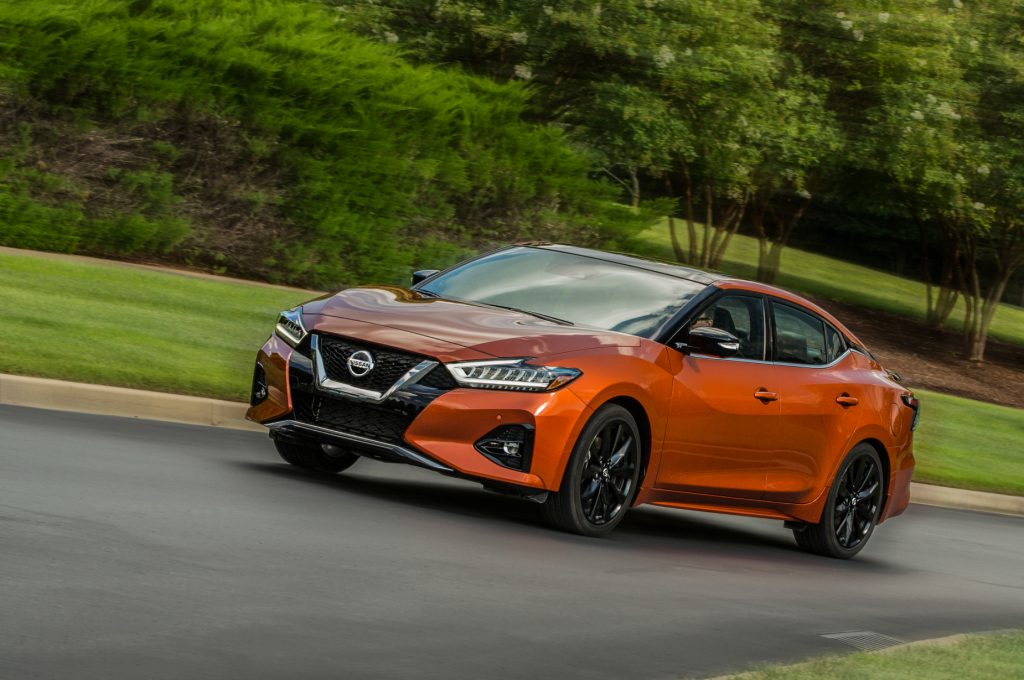 An orange 2020 Nissan Maxima driving down a country road