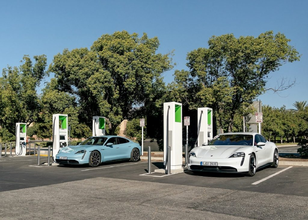 A light-blue and a white 2020 Porsche Taycan 4S at public chargers