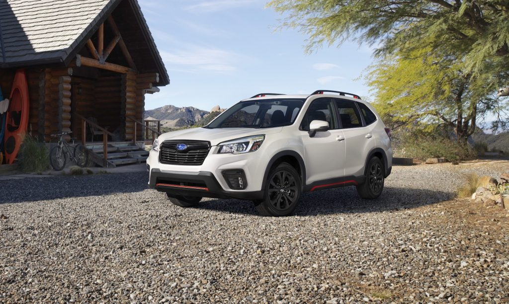 A White Subaru Forester is parked on gravel in front of a log cabin in the mountains.