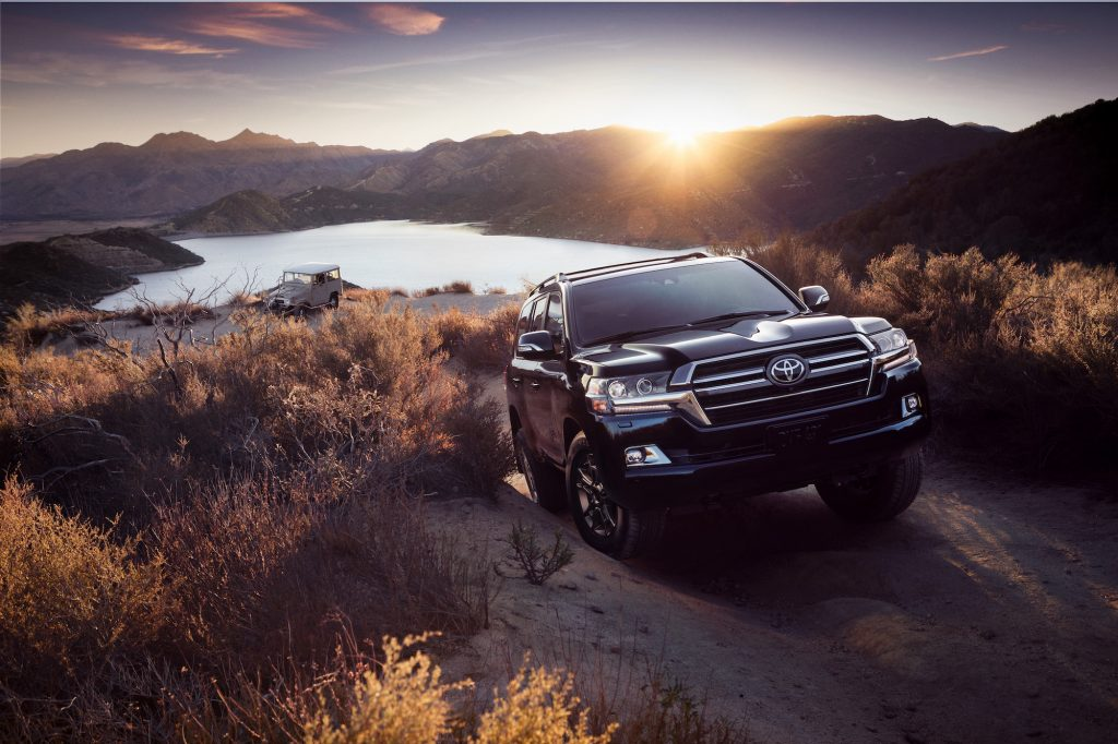 A 2020 Toyota Land Cruiser climbs a hill next to a lake.
