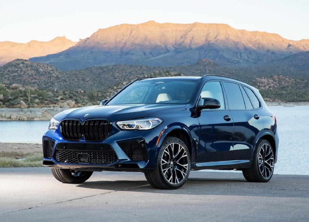 A blue 2021 BMW X5 M Competition by a desert lake
