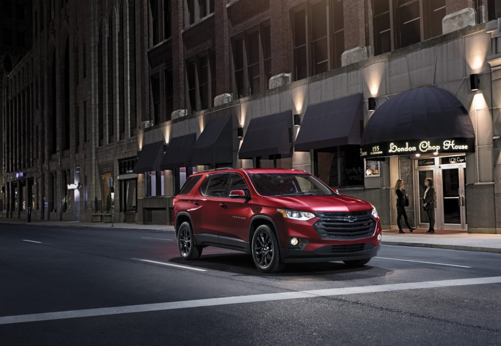 A red 2021 Chevy Traverse midsize SUV driving down a city street