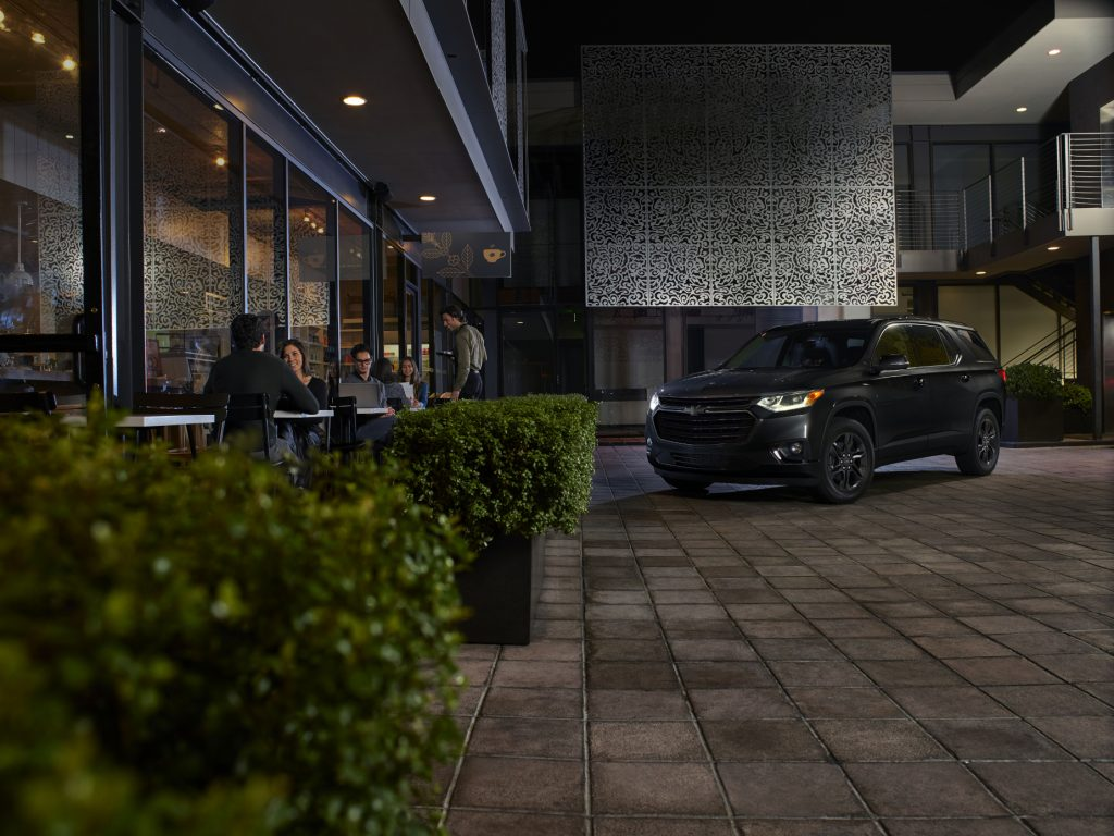 A black 2021 Chevrolet Traverse Midnight Edition parked next to a building