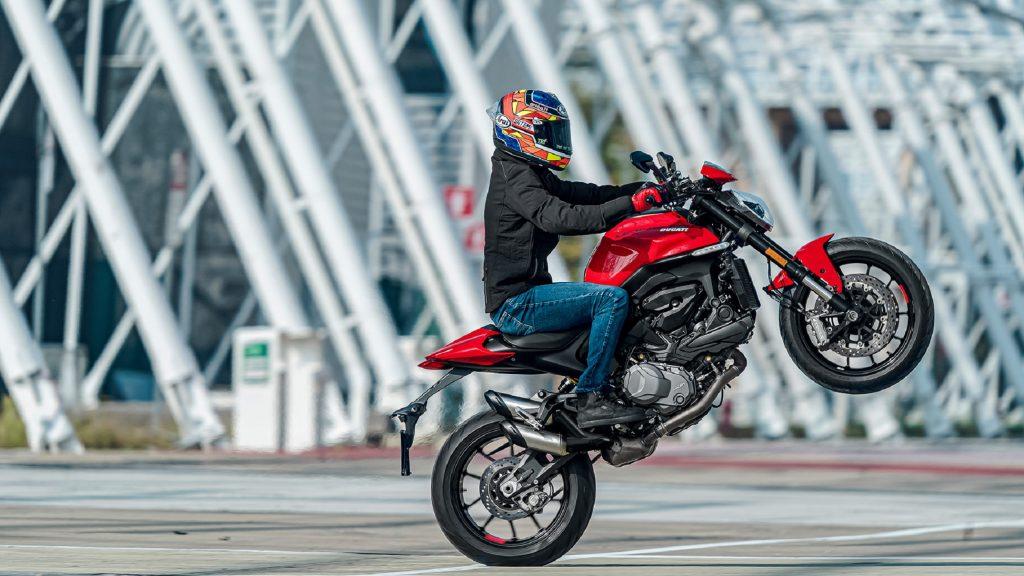 A rider wheelies a red 2021 Ducati Monster Plus