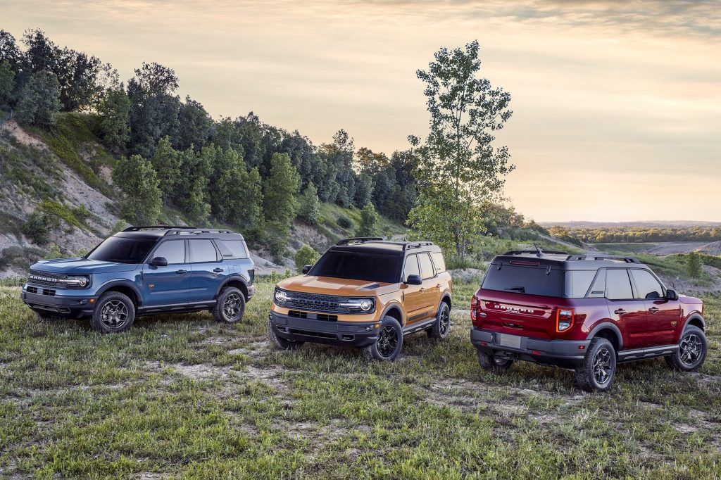 2021 Ford Bronco models in blue, yellow, and red sit on a hillside