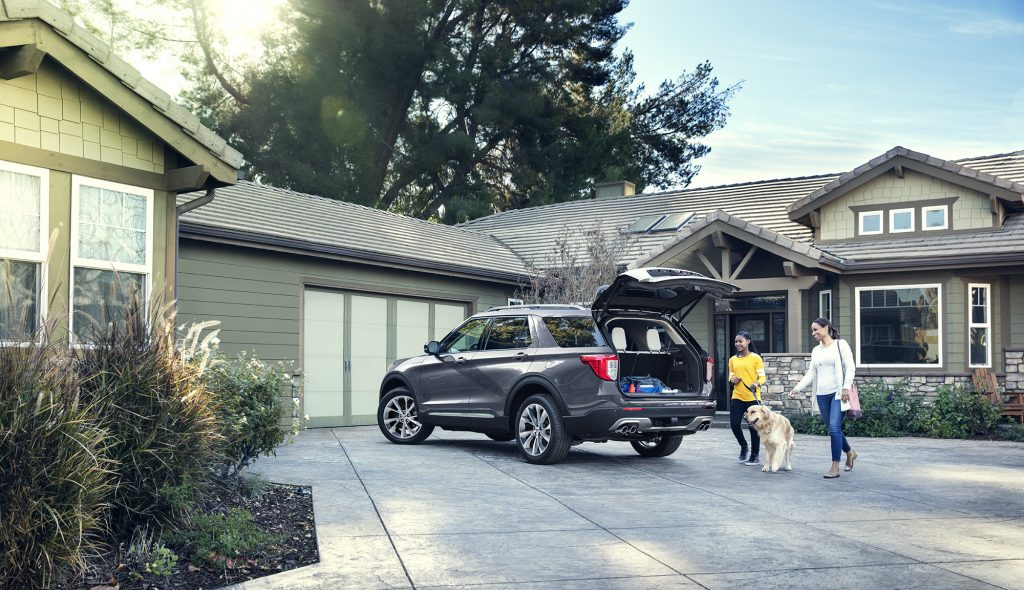 A family unloading the cargo area of a grey 2021 Ford Explorer in their driveway