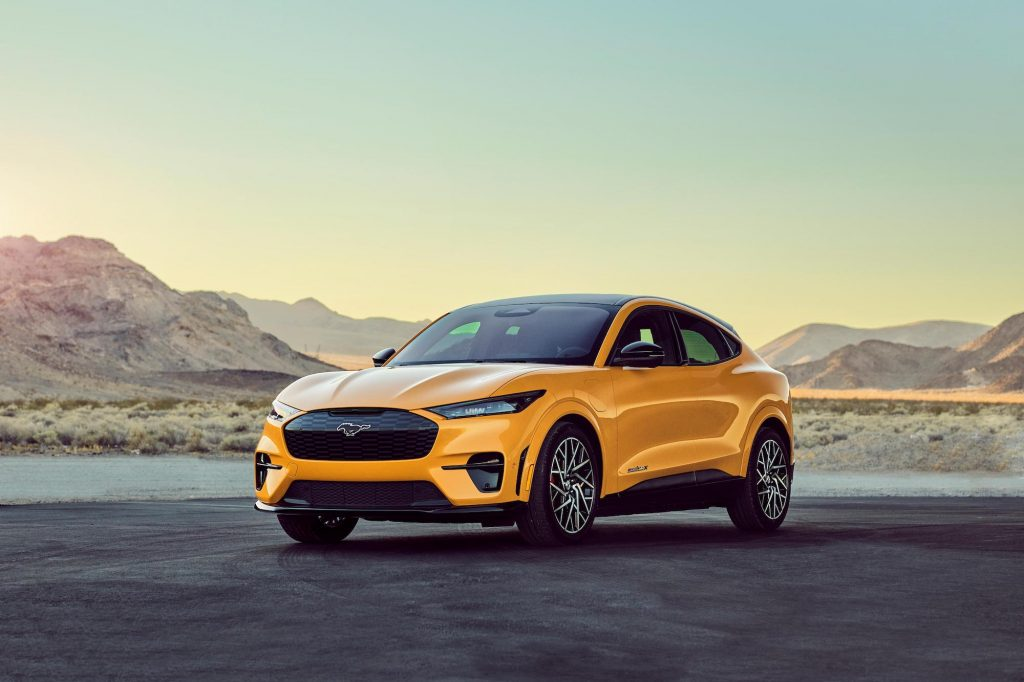 A bright-yellow 2021 Ford Mustang Mach-E GT Performance Edition compact SUV is parked in front of a lake surrounded by mountains on a clear day.
