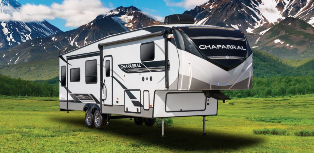 A 2021 Forest River Chaparral Fifth-Wheel RV Trailer sits at the base of a mountainside.