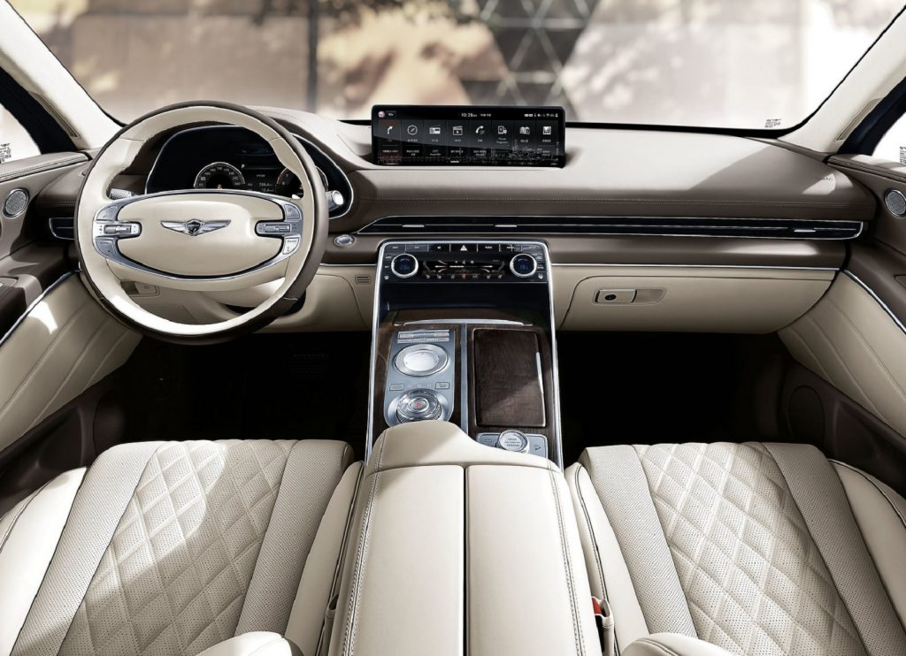 The 2021 Genesis GV80's white-leather front seats and wood-trimmed brown dashboard