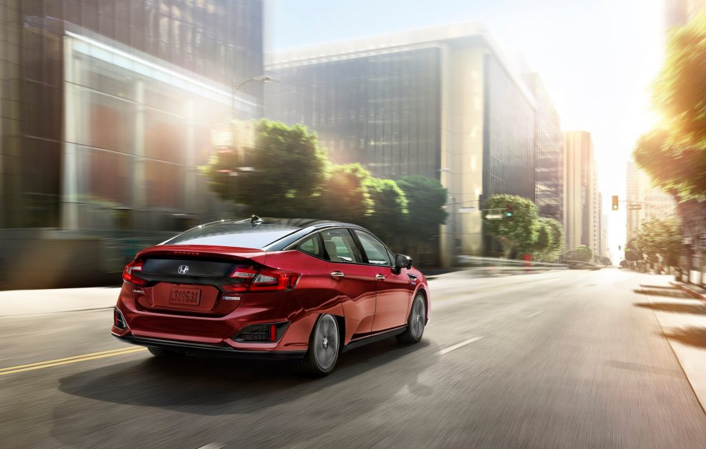 A red 2020 Honda Clarity drives down a city street